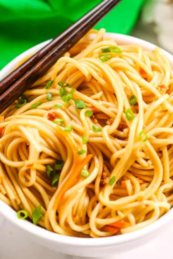 Easy sesame noodles in a white bowl with chopsticks and a green napkin