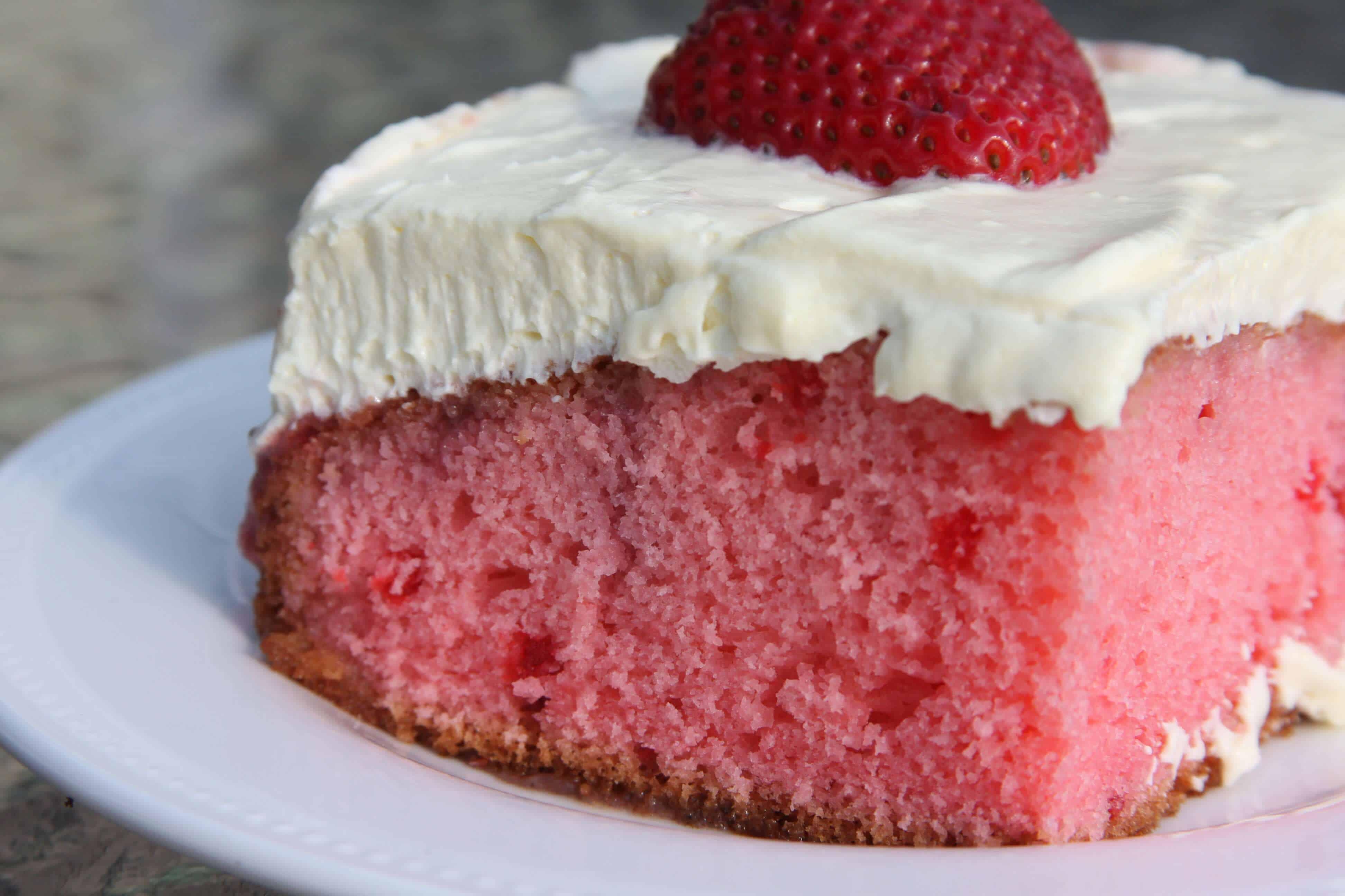 Fresh strawberry poke cake on a white plate