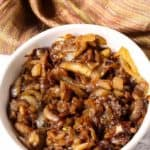 Caramelized onions in a white dish with tan napkin