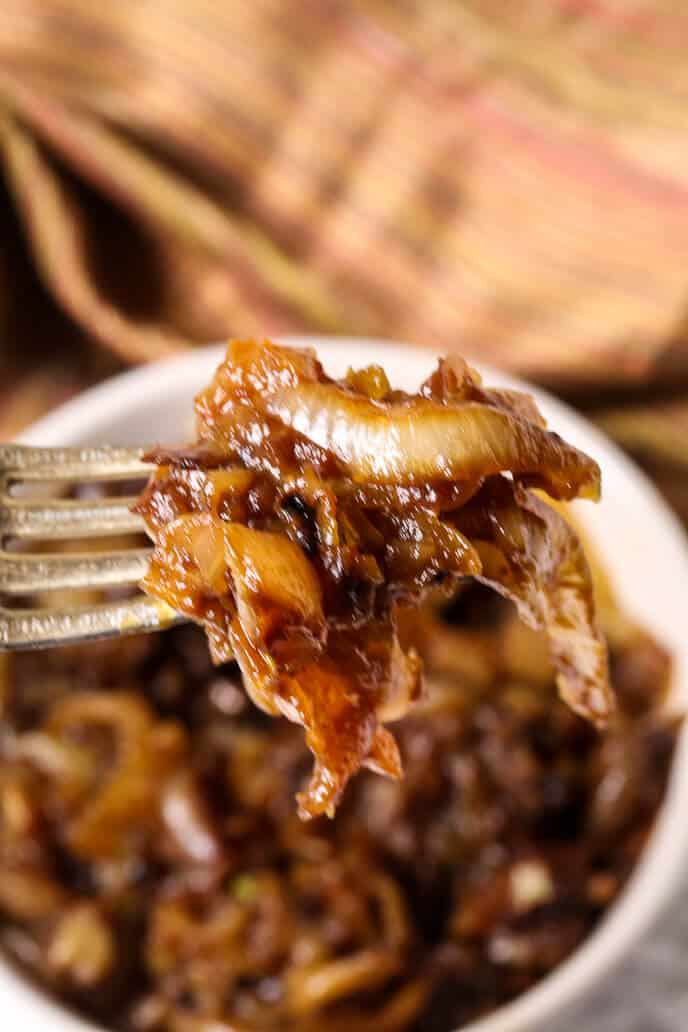 Carmalized onions on a fork from round white dish