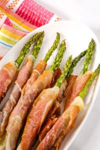 Prosciutto Asparagus on a white plate with a colored napkin
