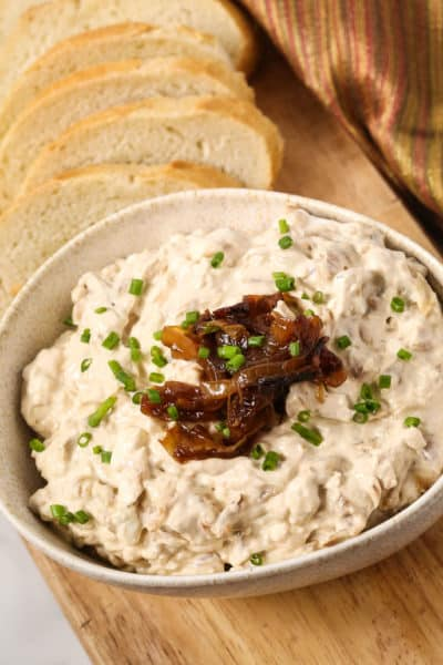 Caramelized onion dip in a white bowl with baguette slices