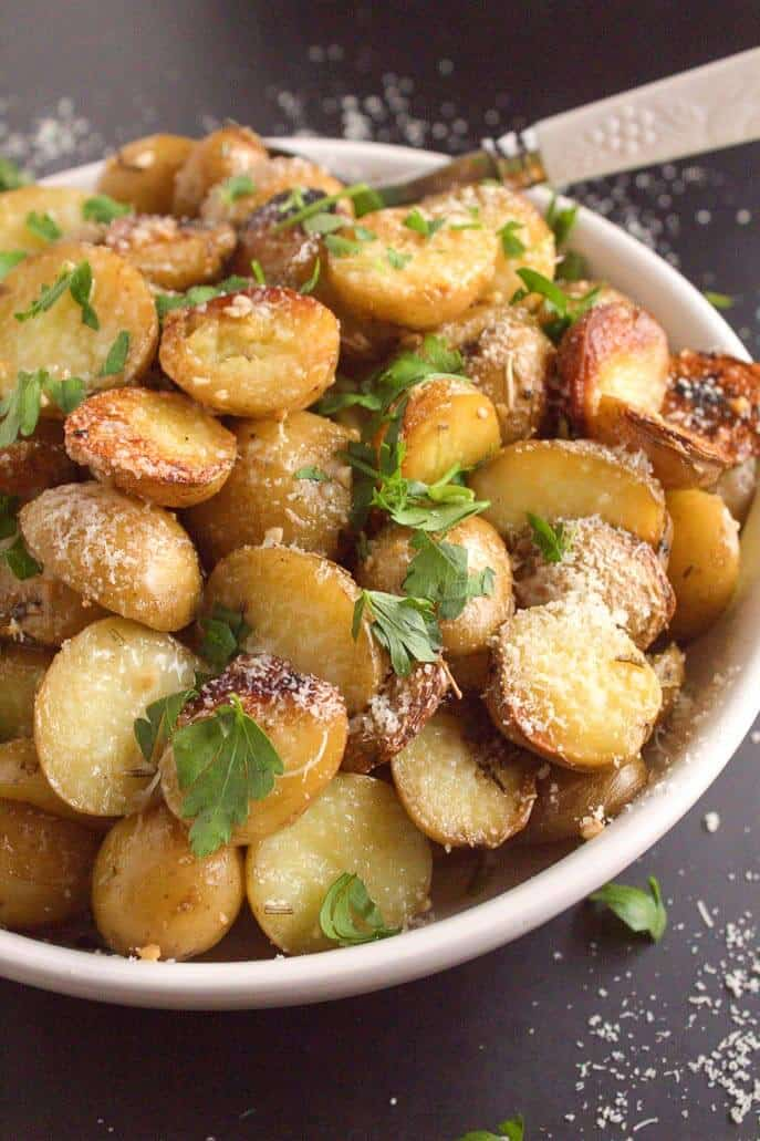 Close up of potatoes in a white bowl on gray counter