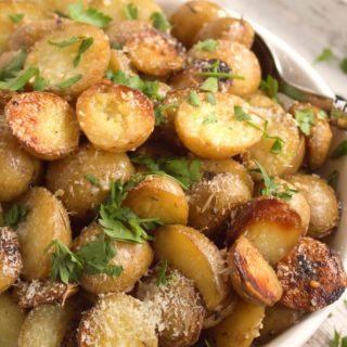 Roast Potatoes with Cheese and Parsley in white bowl