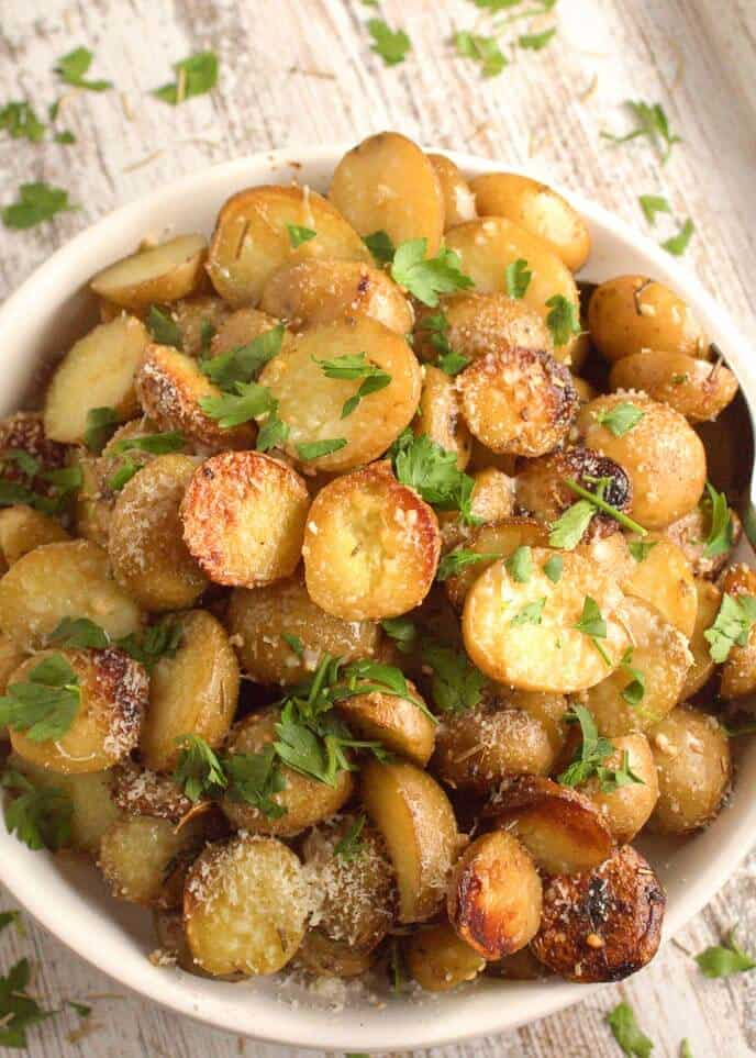 Rosemary Potatoes in white bowl on a marblecounter sprinkled with parsley