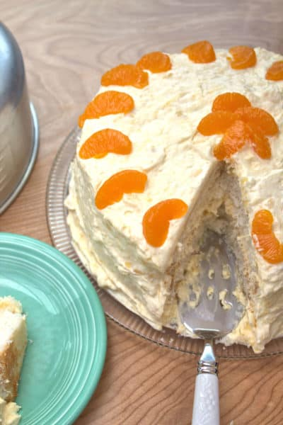 White cake with oranges with slice cut out
