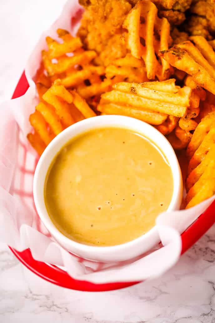 Copycat Chick Fil A Sauce Recipe in a white bowl surrounded by waffle fries