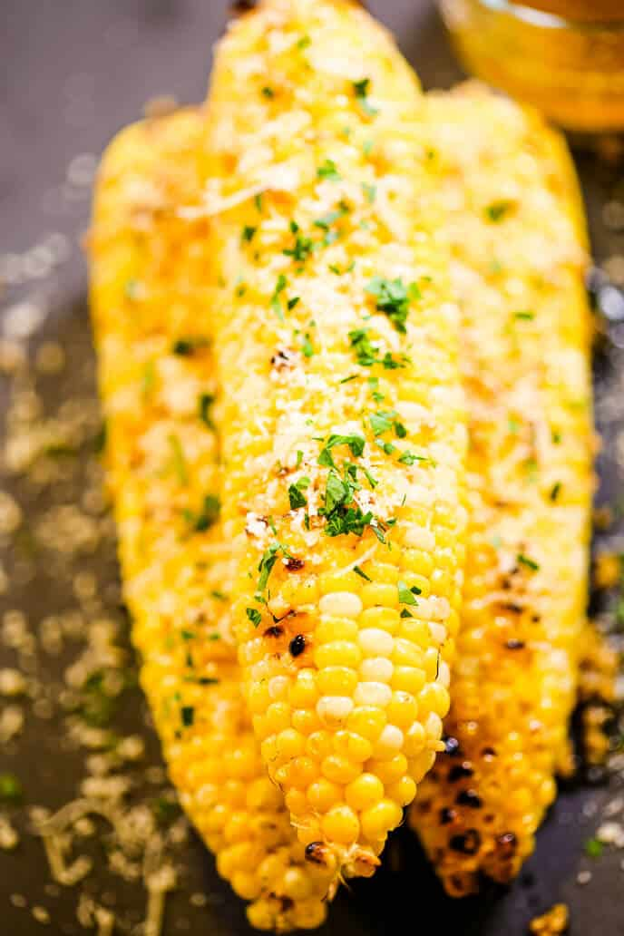Corn on platae sprinkled with cheese and parsley