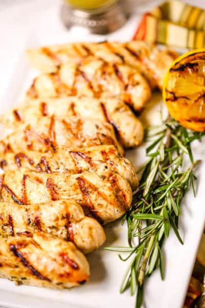 Chicken breast with rosemary on white plate with grilled lemons