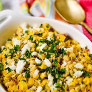 Mexican Corn Salad in a white dish with a gold spoon