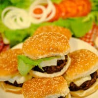 homemade burger recipe on buns with lettuce and tomatoes in background