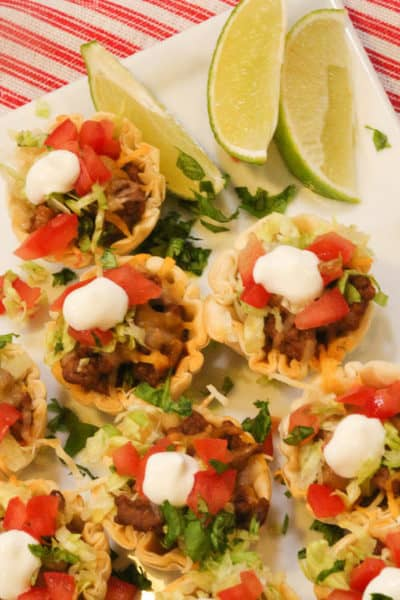 Beef Taco Tarts on a white plate with lime wedges