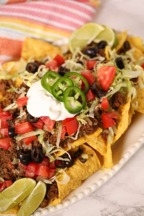 Beef nachos on a white plate with colored napkin