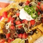 Beef sausage nachos on a white plate with colored napkin