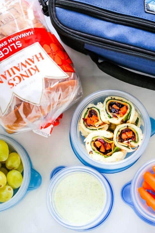 Sandwich sushi in a container with Kings Hawaiian bread, grapes, carrots and dipping sauce