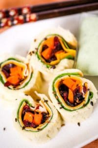 Chicken and cheddar sandwich sushi on a white plate with chopsticks