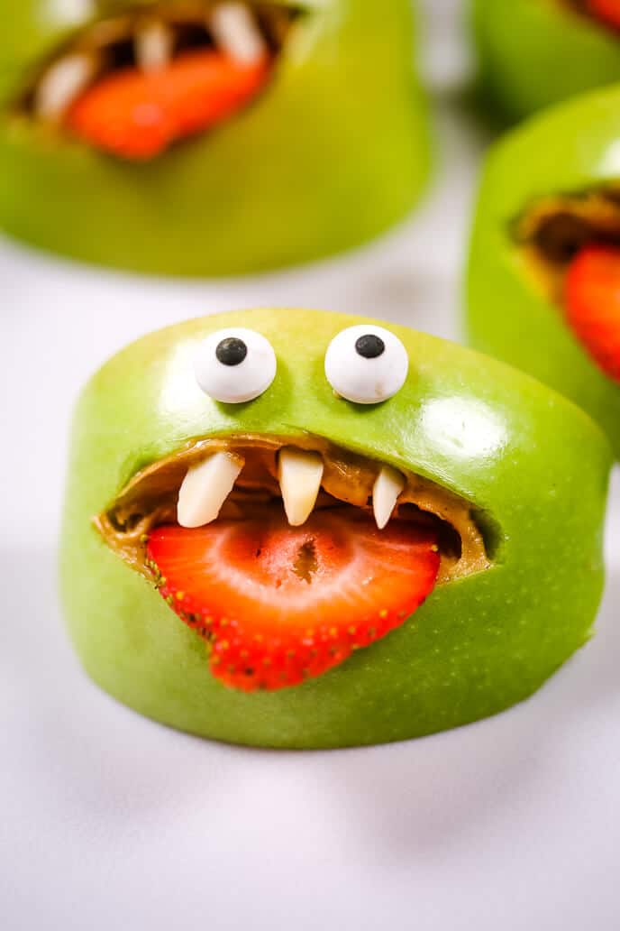 Apple monster halloween snacks on a white table.