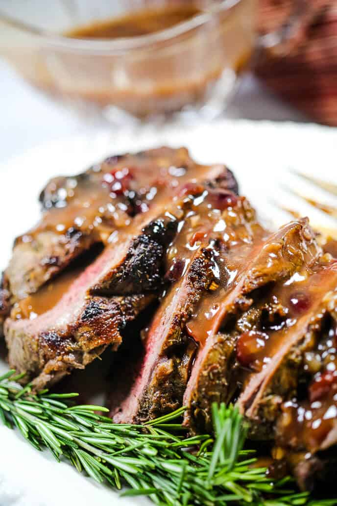 beef tenderloin recipe on a white platter with rosemary sprigs