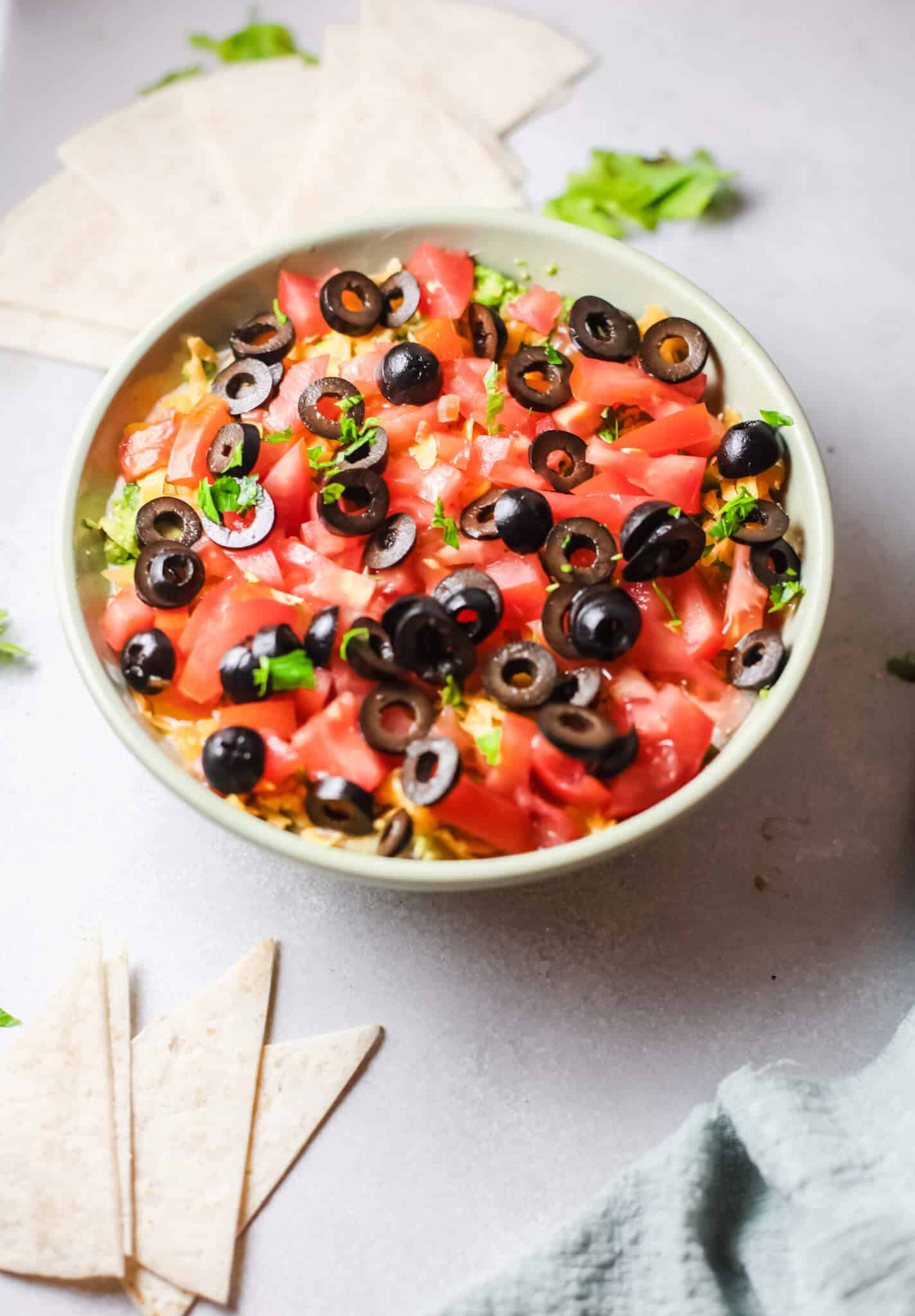 7 Layer Taco Dip in a bowl with pita slices