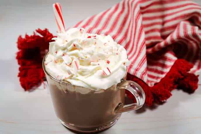 Homemade hot coca recipe in a mug with whipped cream and a candy cane