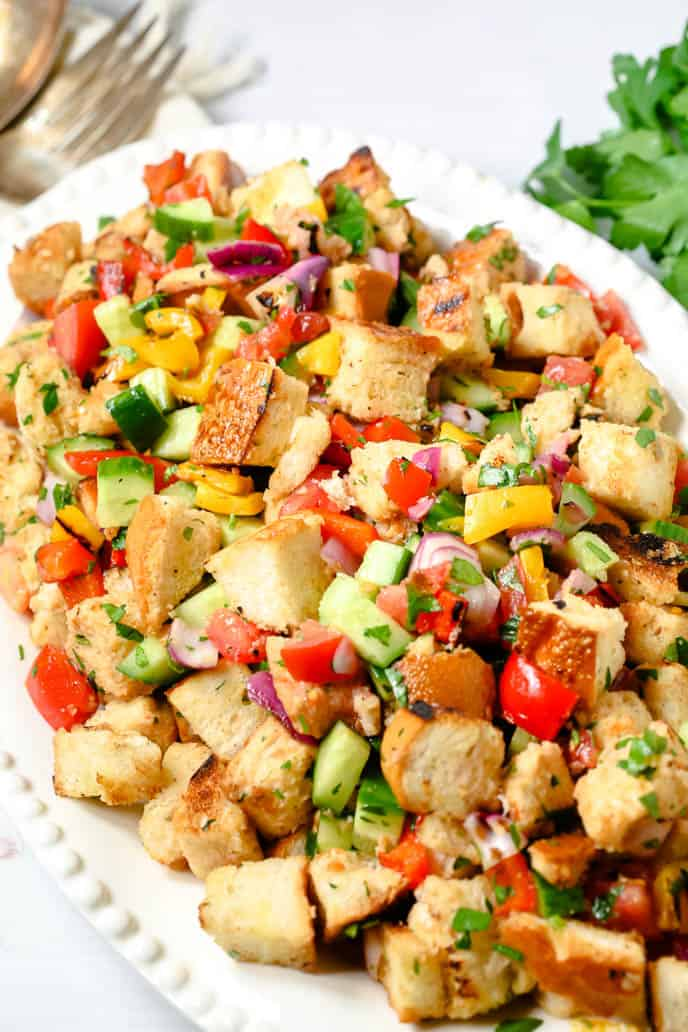 Grilled Panzanella Salad on a white plate with parsley garnish