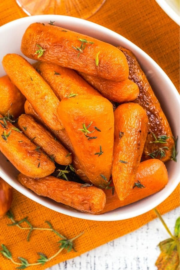 Baby Garlic Roasted Carrots in a white serving bowl topped with herbs