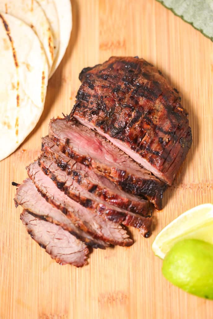 Grilled steak with tortillas and limes on a wooden background