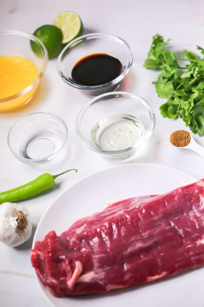 Liquid ingredients for tacos in glass dishes with an uncooked steak on a white plate, surrounded by limes, a pepper, garlic, and cilantro, all on a white background