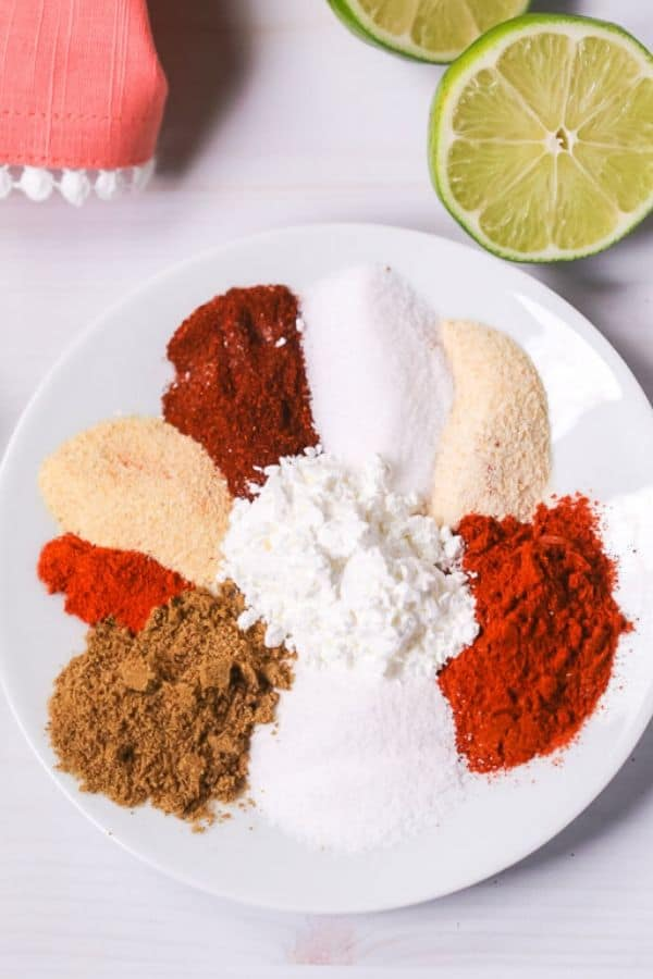 Various spices needed for fajita seasoning on a plate with limes
