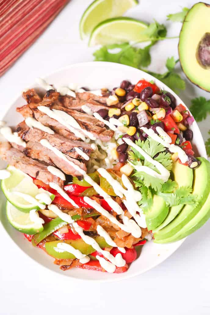 Steak fajita bowl drizzled with dressing and avocado on the side.