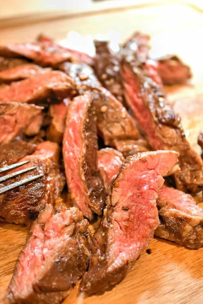 closeup of grilled skirt steak on a wooden cutting board