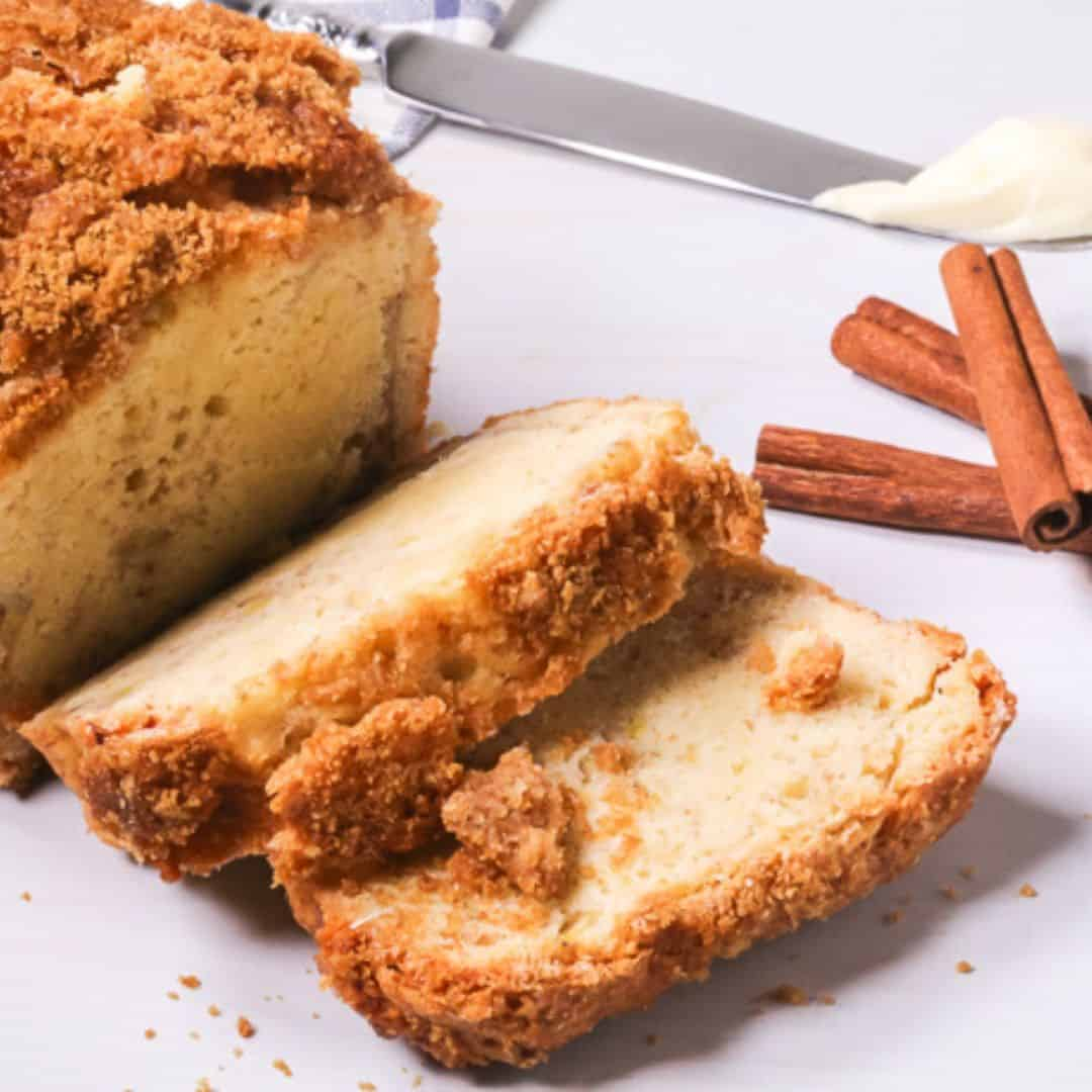 Sliced banana bread on a white table with cinnamon sticks and butter