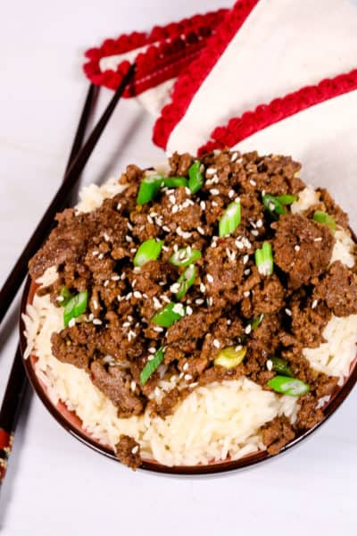 Beef Bulgogi over rice in a black bowl with red and white striped napkin