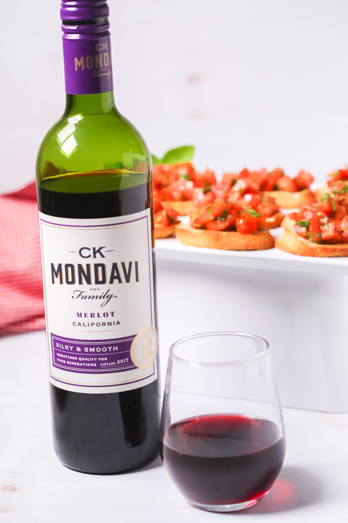 CK Mondavi 2017 Merlot in a bottle and glass with tomato bruschetta behind it.