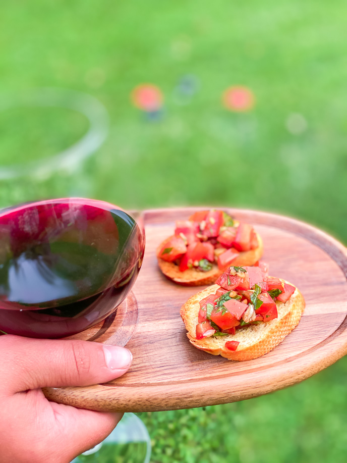 Tomato basil bruschetta with wine on a wooden plate