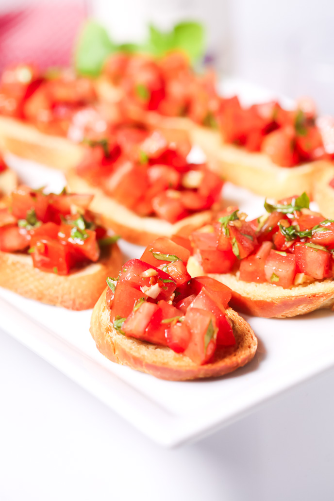 Fresh tomato bruschetta with basil on a white plate.