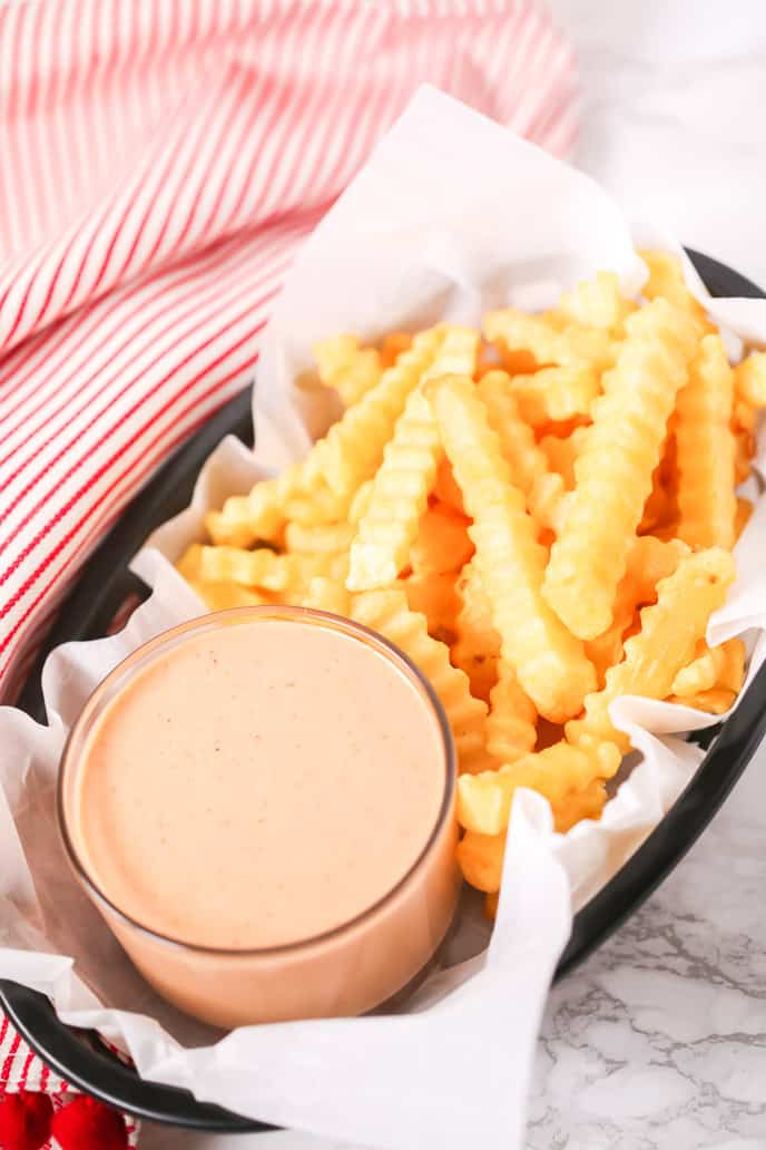 Basket of fries with red and white stripped napkin with fry sauce