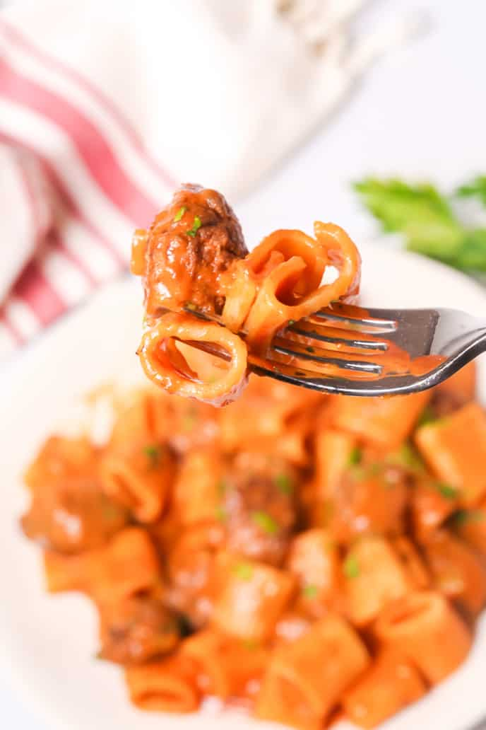 Fork of Italian Sausage Pasta recipe with plate in background