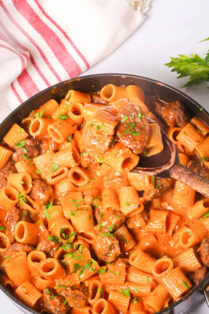Pan of Italian Sausage Pasta with red and white napkin and wooden spoon