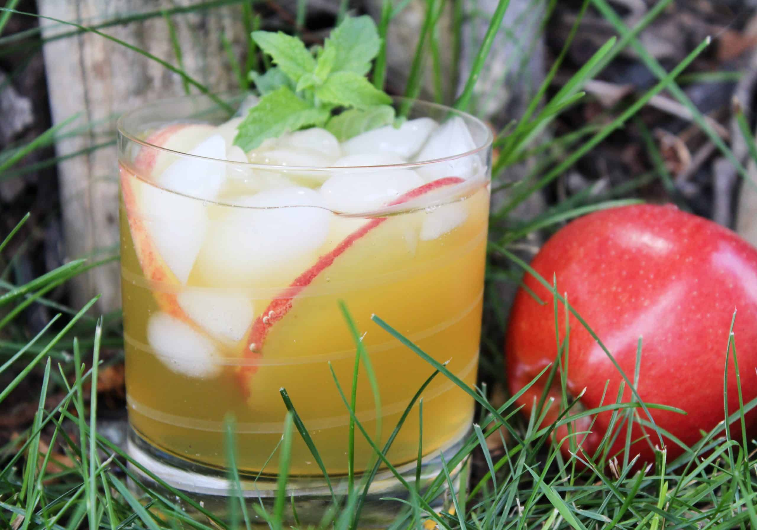 Apple cider mojito in a glass with an apple on the side.