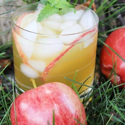 Apple Cider Mojito in a glass with 2 apples on the side