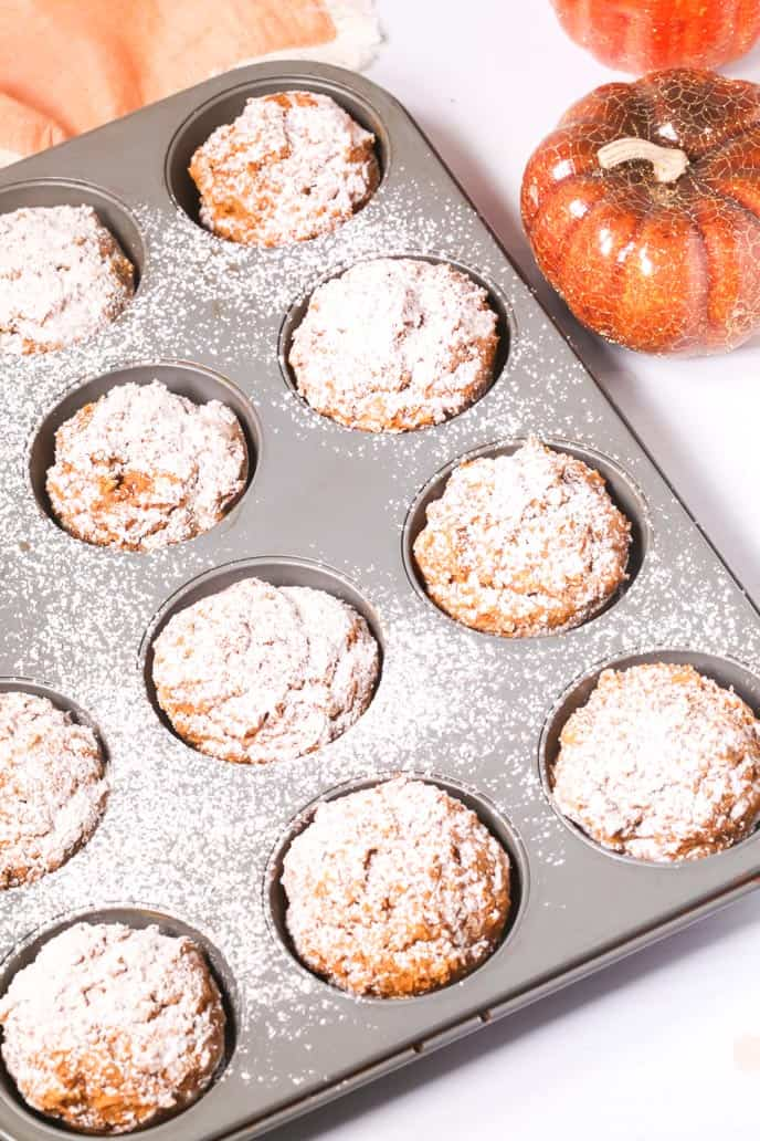 Easy pumpkin muffins in a muffin tin with powdered sugar on top and a pumpkin on the side.