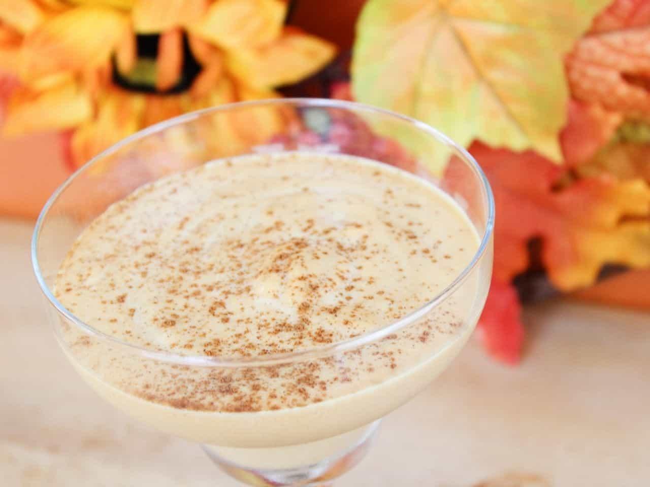 Pumpkin cocktail milkshake in a glass with leaves behind it