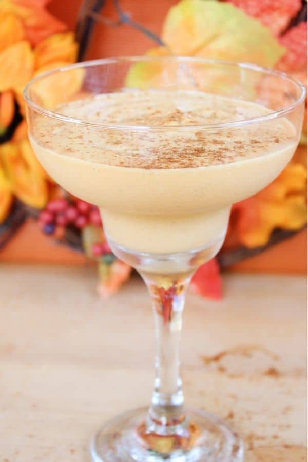 Spiked pumpkin milkshake in a glass with leaves behind it.
