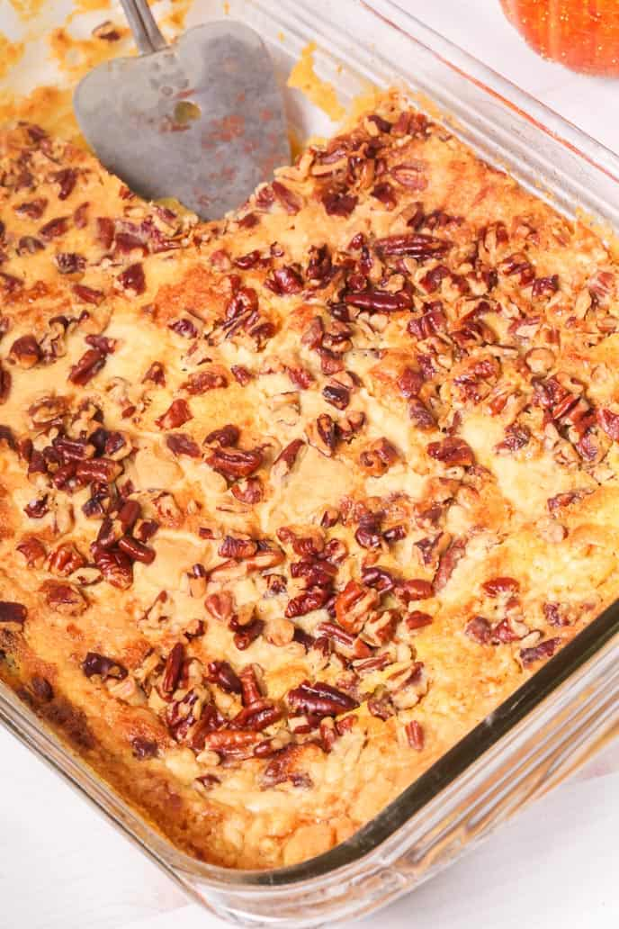 Pumpkin cake recipe with pecans in a baking dish with a spatula.