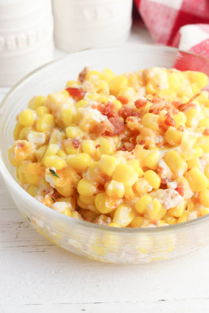 Cheesy Bacon and Corn Casserole in a bowl with a checkered towel