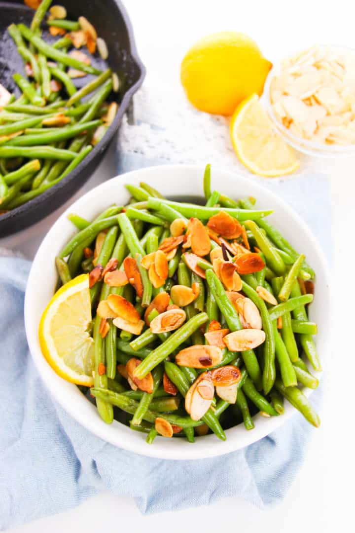 Green bean almondine in a white bowl with extras in a skillet
