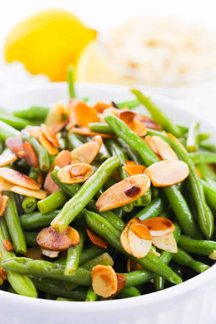 Close up of green beans almondine in a white bowl with a lemon in background