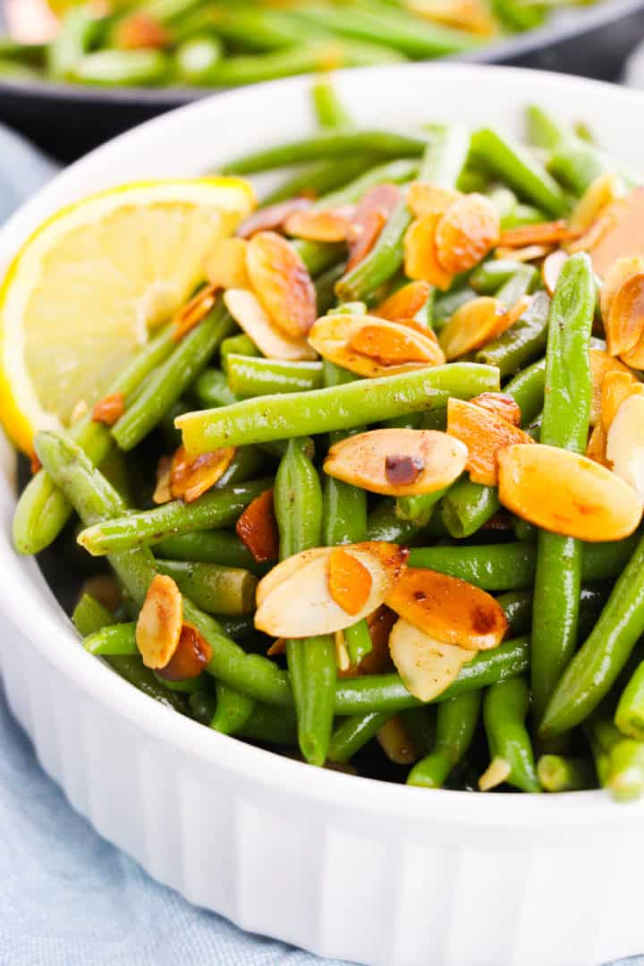 Green beans almondine in a while bowl with a lemon wedge