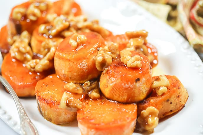melting baked sweet potato recipe on a white platter with walnuts on top